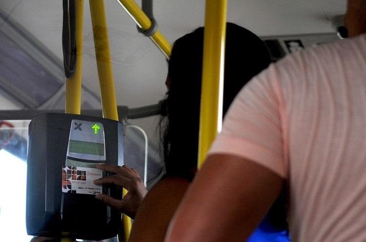 Foto de uma mulher passando o cartão especial no leitor do ônibus