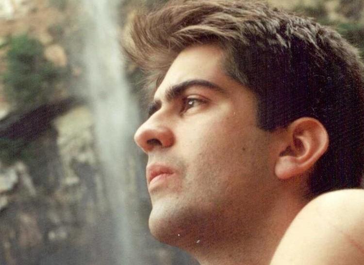 Foto de Ricky Ribeiro, um jovem branco, de cabelos e olhos castanhos. Ele olha para o lado esquerdo e está de perfil, com uma expressão contemplativa