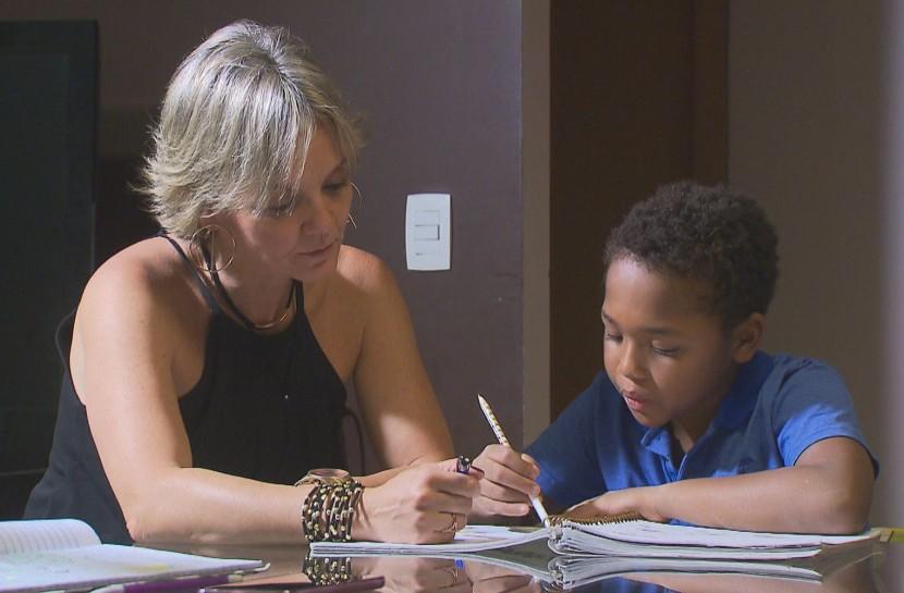 Foto de uma mulher loira ajudando um garoto negro com o dever de casa.