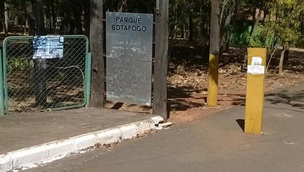 Foto do parque, com a placa em evidência, ao lado de um portão verde e uma calçada desnivelada