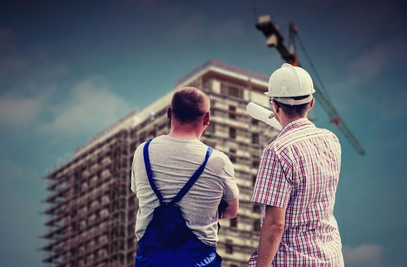 Foto de dois homens em pé olhando um prédio. Um deles está usando macacão e outro está usando blusa social. Um deles está com capacete branco na cabeça.