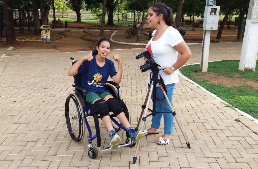 Foto de duas mulheres. A da esquerda está em uma cadeira de rodas e a da direita, cega, está com uma câmera em um tripé.