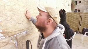 Foto de Tony visto de lado, tocando com a mão direita no Muro das Lamentações. Ele está de moletom cinza e boné bege. Em sua orelha esquerda, usa um aparelho auditivo.