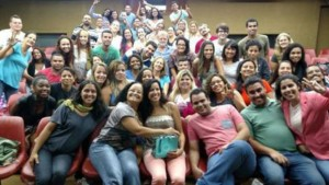 Foto de grupo de pessoas sorrindo para retrato dentro de um auditório
