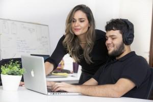Foto de uma mulher e um jovem cego navegando em um computador. Ela tem cabelos longos e claros e olha na direção do computador. Ele é branco, de cabelos curtos e escuros e usa um fone enquanto navega, de olhos fechados