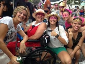 Foto de um grupo de cinco mulheres, com os rostos pintados e chapéus. Uma delas é cadeirante e elas participam de um bloco de rua