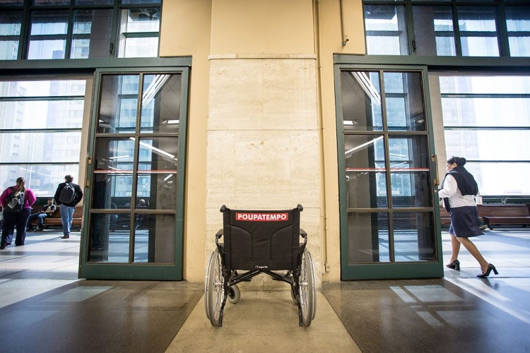 Foto de um espaço amplo e iluminado, com uma cadeira de rodas parada em frente a um elevador
