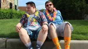 Dois homens sentados na sarjeta, com colares havaianos, camisas e meias coloridas. Da esquerda para a direita: um jovem, com síndrome de down, branco com cabelos curtos e escuros; um homem de meia idade, branco com cabelos grisalhos e óculos escuros