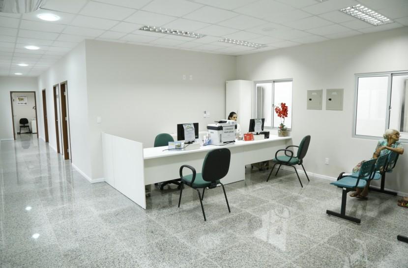 Foto de uma sala fechada, branca , com uma mesa de atendimento e cadeiras vazias