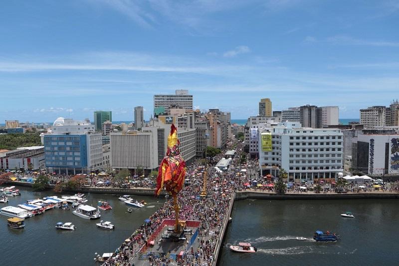 Foto aérea do porto de Recife, com prédios e barcos vistos de cima. No céu, há um enorme balão em formato de galo