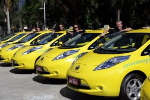 Foto de uma frota de táxis amarelos, em fila, com pessoas de diversas idades, ao lado das porta do motorista de cada veículo