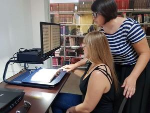 Foto de duas mulheres em uma biblioteca, com dispositivos acessíveis para leitura à frente.