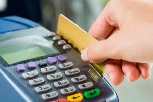 Foto em close de uma mão passando um cartão em uma maquineta