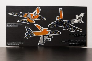 Foto de um grande painel preto, com três aviões voando em diferentes direções. Os aviões são feitos de tecido, plástico e outros materiais com diferentes texturas, em laranja, azul, detalhes em dourado, prateado e plástico-bolha. Há dizeres em braile, com o texto: Obra Tapete Voador I, II e III; artista: Alex Flemming; adaptação tátil: Marina Baffini