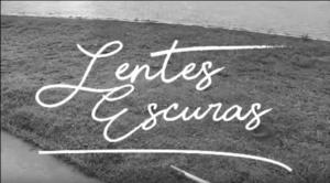Arte de foto em preto e branco, com uma bengala de cego tateando o chão. Sobre a imagem, há os dizeres, em letra cursiva: Lentes Escuras