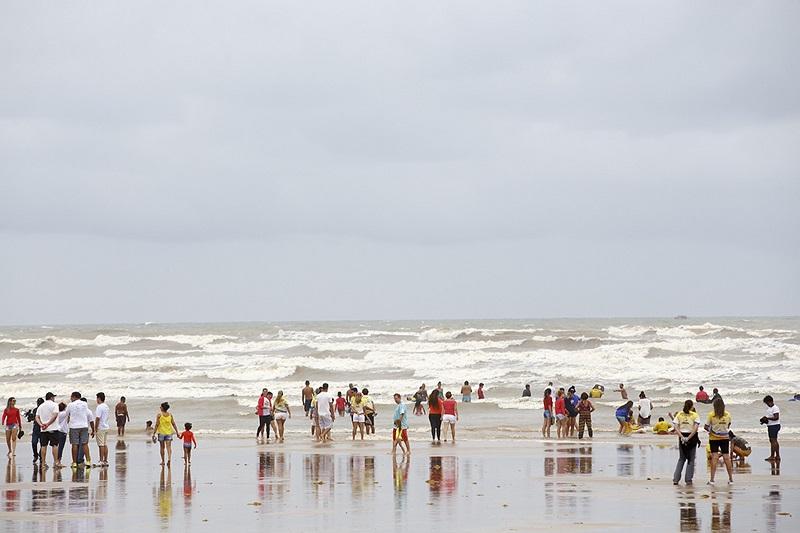 Foto em plano aberto de uma praia com diversas pessoas na parte rasa do mar