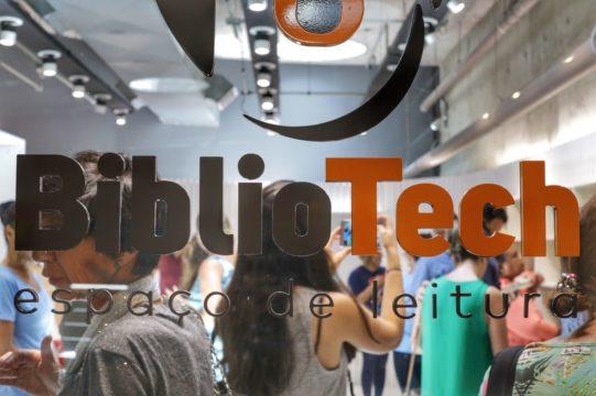 Foto do logo da BiblioTech em uma parede de vidro. Atrás, pessoas de diversas idades circulam pelo ambiente