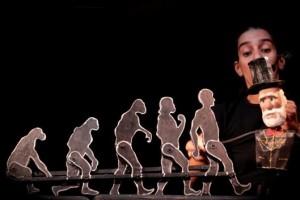 Foto em close de marionetes articulados em fila, indicando a evolução do macaco até o homem. No lado direito, há um boneco de Charles Darwin, um senhor com cartola e longa barba branca