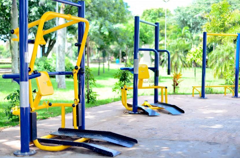 Foto de três equipamentos de musculação adaptados para cadeirantes em uma praça ao ar livre