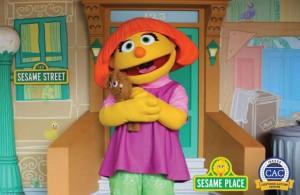 Foto da personagem Julia, da Vila Sésamo, segurando um ursinho de pelúcia. Ela tem uma aparência lúdica, com uma cabeça grande e amarela, nariz e cabelos laranja