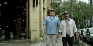 """Cena do filme """"Teu mundo não cabe nos meus olhos"""". O ator Edson Celulari, um homem de 60 anos, branco, com olhos azuis, caminha pela rua, com uma bengala para cegos, acompanhado de um home mais novo, de boina e um bigode escuro e espesso."""