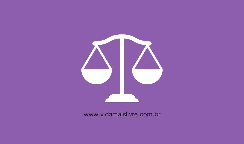 Em fundo roxo, ícone em branco que representa a balança da justiça