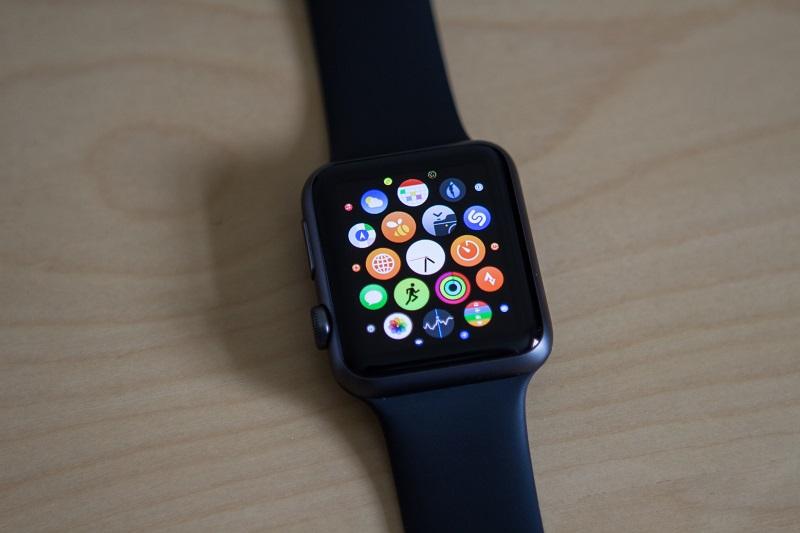 Foto do Apple Watch apoiado em uma mesa. Ele tem a cor cinza espacial e seu displau exibe ícones diversos de aplicativos