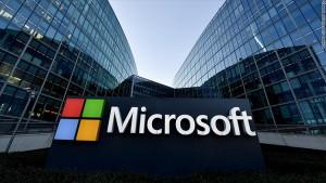 Fachada de dois prédios espelhados, com o logo da Microsoft em destaque. quatro quadrados - vermelho, verde, azul e amarelo formam uma janela. Ao lado, há a palavra Microsoft em branco