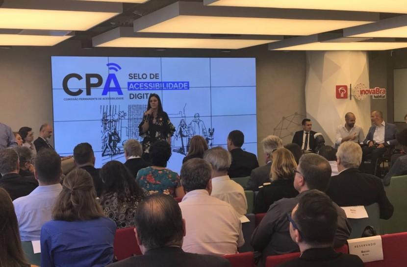 """Em um auditório fechado, uma mulher se apresenta ao público. Ela é alta, morena e está de pé. Na tela ao fundo, há o texto """"CPA e Selo de Acessibilidade Digital"""""""