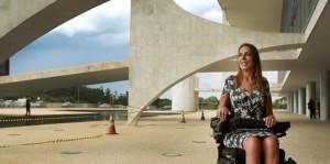 Mara, uma mulher branca e loira, sentada em uma cadeira de rodas, sorrindo e olhando para o lado esquerdo. Ao fundo, o Palácio do Planalto