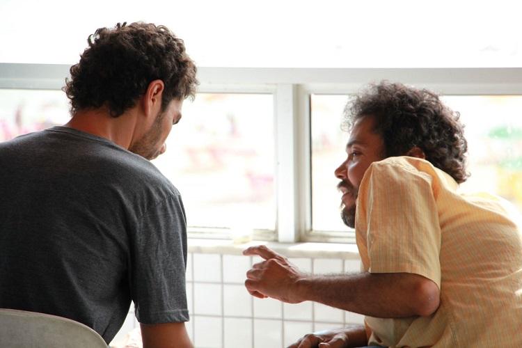Foto em plano médio fechado de dois homens jovens sentados conversando em frente à uma janela