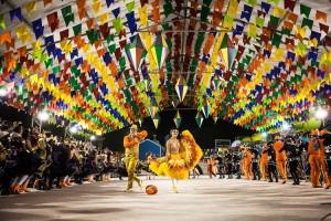 Foto em plano aberto da Festa de São João de Caruaru. Entre bandeirinhas, há um casal com trajes de frevo dançando em um grande corredor, rodeado de pessoas