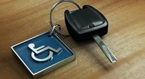 Foto de uma chave de carro presa a um chaveiro de metal quadrado; ele é azul e tem o símbolo de pessoa com deficiência física