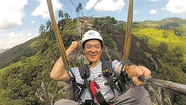 Foto de um homem com traços orientais pendurado na tirolesa. Ele sorri e faz uma selfie