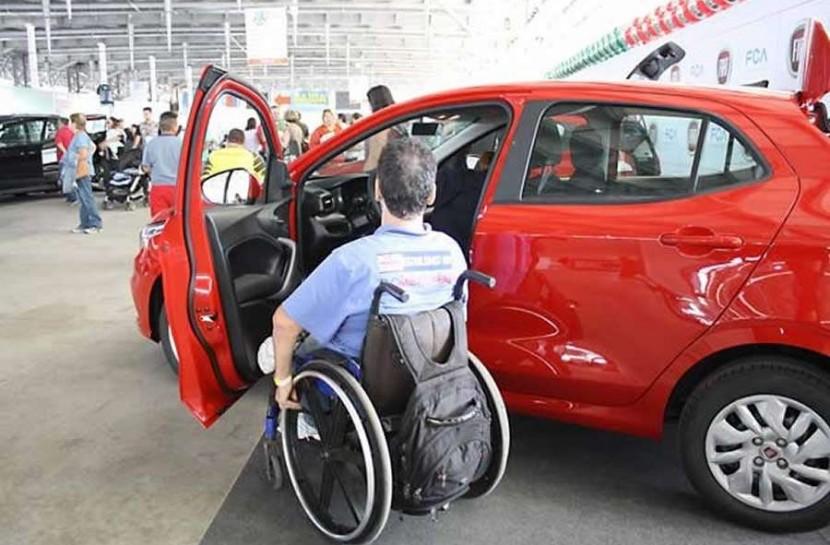 Foto em uma grande feira, com um homem cadeirante entrando em um carro vermelho