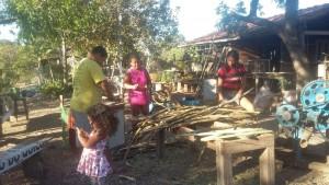 Foto do assentamento, com um grupo de pessoas de diversas idades reunido ao ar livre em torno de uma estrutura de madeira