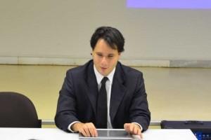 Foto de Leonardo Coscarelli, um homem jovem, branco, com cabelos escuros na altura do queixo. Ele usa terno e gravata azuis e camisa branca, está sentado atrás de uma mesa