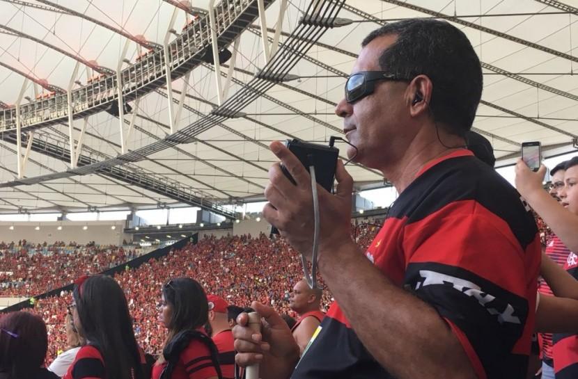 Foto de um homem em pé na arquibancada, segurando um radinho de pilha. Ele veste uma camisa do Flamengo