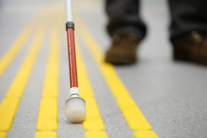 Foto que destaca uma bengala de pessoa com deficiência visual sendo utilizada sobre piso tátil. Ao fundo, em desfoque, os pés de uma pessoa