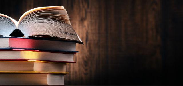 Foto de livros empilhados sobre uma textura que imita madeira