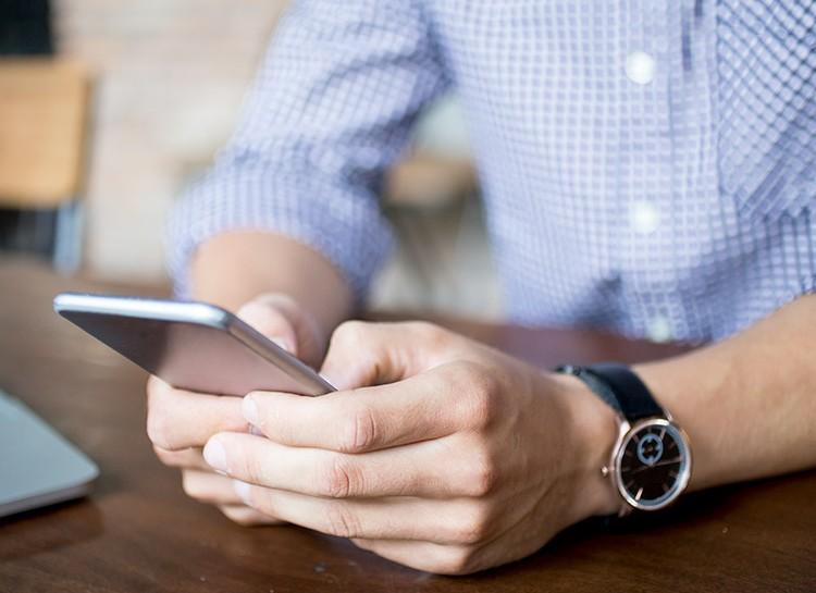 Foto de mãos de um homem segurando um celular