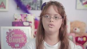 Foto de uma jovem com Down. Ela tem cabelos longos castanho avermelhados, usa óculos e está em um ambiente fechado repleto de pôsteres coloridos ao fundo
