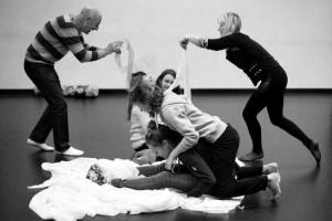 Foto em preto de branco de uma oficina de dança com pessoas de diversas idades
