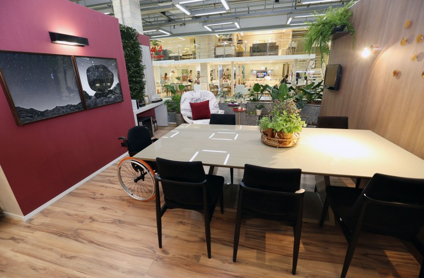 Foto de uma sala de jantar com uma mesa retangular, cadeiras pretas e, na pota da mesa, uma cadeira de rodas