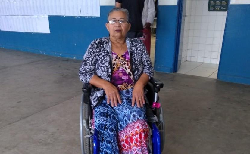 Foto de uma senhora de 60 anos. Ela é cadeirante, em cabelos grisalho preso, usa óculos e usa um vestido colorido