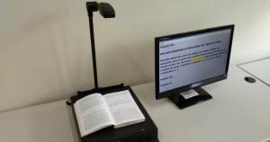 Foto do leitor autônomo. Sobre sua superfície, há um livro aberto e, ao lado, uma tela exibe o conteúdo em texto do livro.