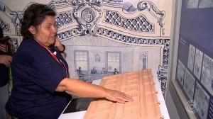 Foto de uma senhora cega tateando réplicas em relevo dos desenhos de azulejos portugueses