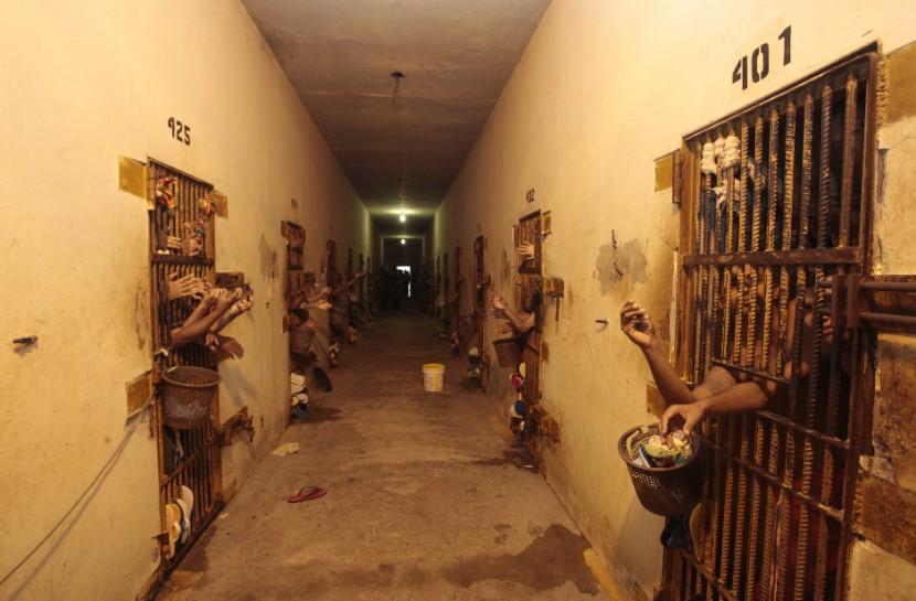 Corredor de um presídio com pouca iluminação, paredes descascadas e braços de pessoas saindo pelas celas