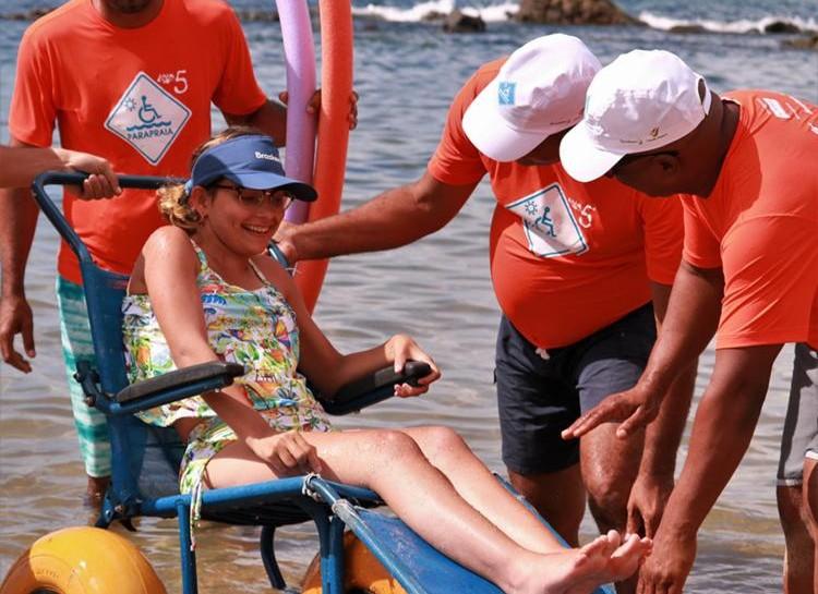 Mulher jovem em cadeira de rodas anfíbia na beira do mar. Ao seu redor, há três homens dando suporte. Eles usam camisetas do projeto Para Praia.