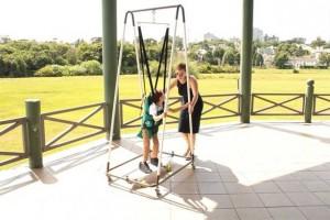 Foto de uma criança brincando em balanço adaptado com cinta de segurança e suportes para sustentação da coluna